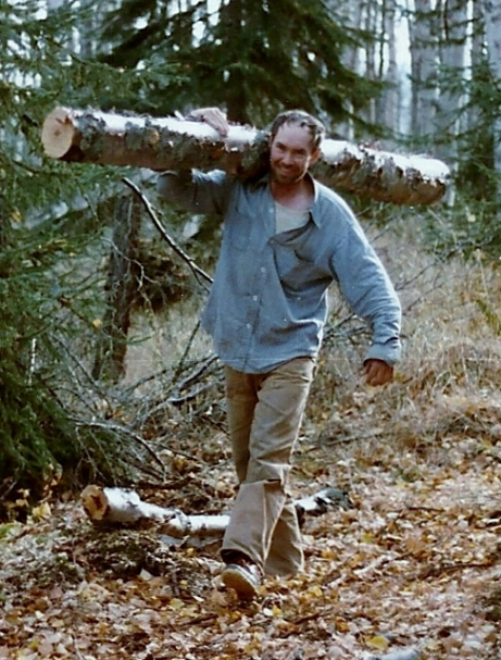 Sam carrying a log that will be used for firewood.