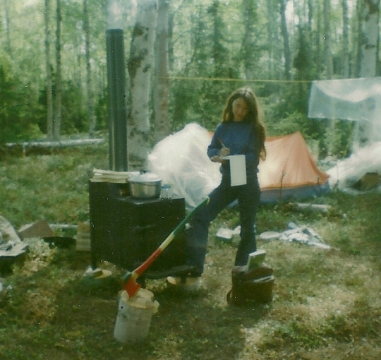 Writing letters to the loved ones back home. The pup tent in the background was home for three months. Pot of beans is cooking on the wood stove. The plastic sheeting behind me is used to cover the tent when it rains.