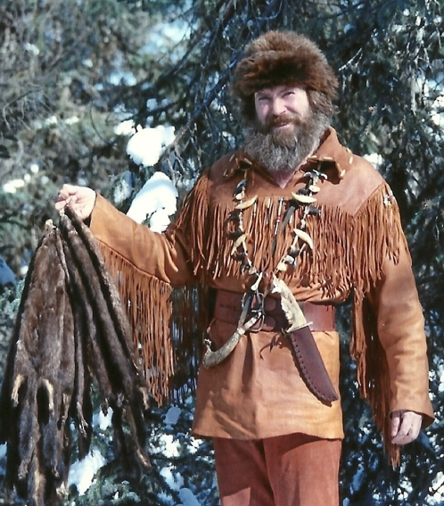 Trapper Sam holding up a string of mink pelts! Notice the Bear jaw handled knife he made?